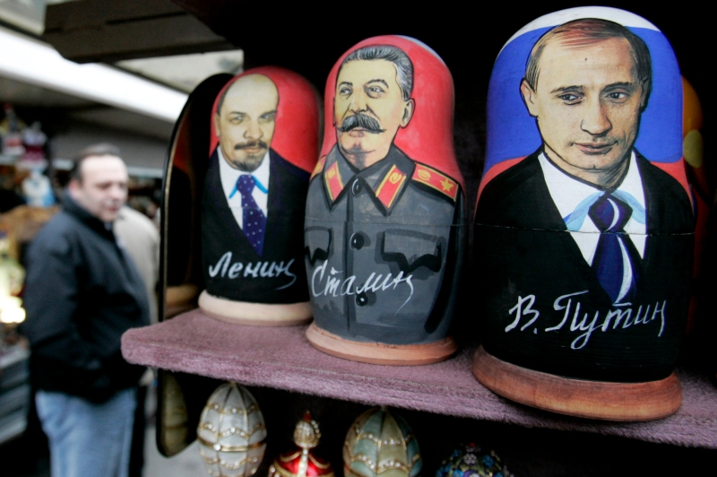 Customers walk past a shop with Russian matryoshka dolls decorated with portraits of Lenin, Stalin and Putin  at a market in the centre of St.Petersburg