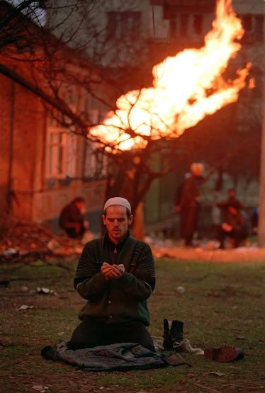 Un uomo prega durante la battaglia di Groznyj
